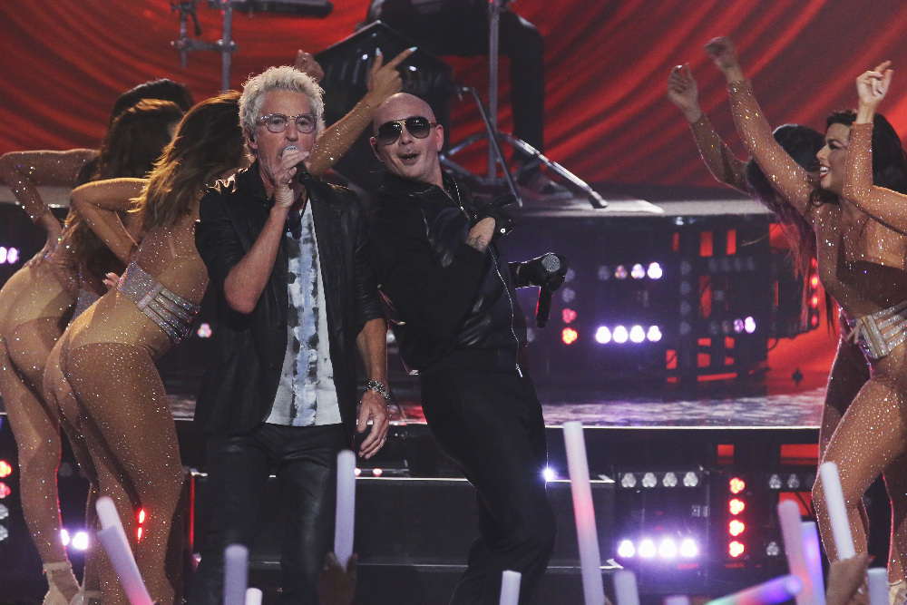 Pitbull joins REO Speedwagon on stage.